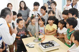 LPガスの液体が気体に変わるのを見て驚く子どもたち=長崎県松浦市の九州液化瓦斯福島基地