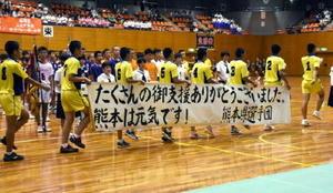「たくさんの御支援ありがとうございました。熊本は元気です!」とメッセージを添えた横断幕を持って行進する熊本県選手団=県総合体育館