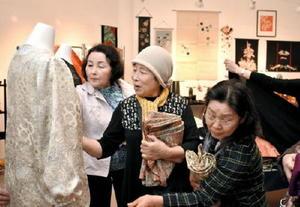 着物の生地で作られたワンピースを見て楽しむ来場者=佐賀新聞ギャラリー
