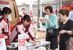 新旧のコーヒーを飲み比べる来店客=佐賀市のセブン―イレブン佐賀高木瀬長瀬店