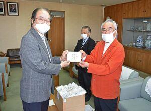伊万里市に手作りマスク500枚と生地を寄贈した松永一広さん(右)。左は深浦弘信市長=市役所