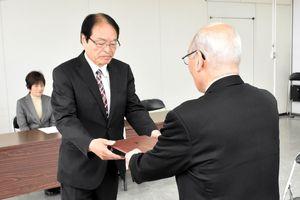 伊万里市選管から市長選の当選証書を受け取る深浦弘信氏=伊万里市役所