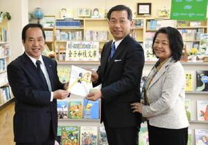 塚部芳和市長に寄付金の目録を手渡す金子和斗志さん(中央)。右は妻の晴美さん=伊万里市の黒川小