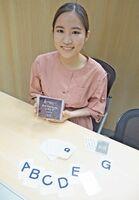 商品化したアルファベット・トランプを手にする原口桜さん