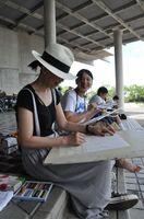 日陰で集中して描く参加者=佐賀市の県立博物館、美術館周辺