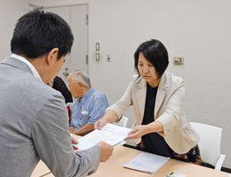 佐賀県人事課職員(左)に要望書を提出する興梠多津子会長=県庁