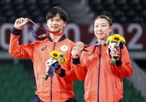 混合ダブルスで獲得した銅メダルを掲げる渡辺勇大(左)、東野有紗組=武蔵野の森総合スポーツプラザ