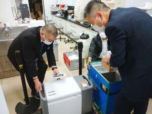 ワクチンを冷凍庫に搬入する日本体育大関係者(左)ら=18日午前、東京都世田谷区の日体大