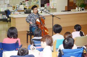 チェロ奏者の九十九太一さん(奥)の演奏に聴き入る子どもたち=佐賀市の佐賀整肢学園こども発達医療センター