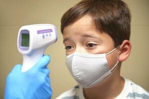 新型コロナウイルスの検査で、検温を受ける男の子=2020年11月、ロンドン近郊(ゲッティ=共同)