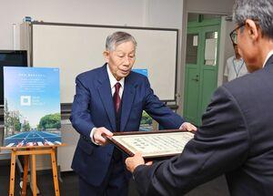 落合裕二県民環境部長から感謝状を受け取る村瀬勲さん(左)=佐賀県庁