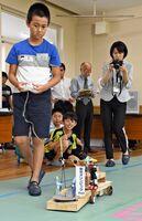 東京オリンピックをイメージして、フェンシングや卓球を打ち合うからくりをペアで作り、操縦する岡元太郎君=佐賀市成章町の勧興小学校