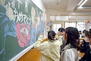 教室に用意された黒板アートに見入る児童ら=佐賀市の新栄小