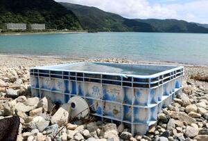 東日本大震災の津波で宮城県石巻市から流された石巻魚市場のプラスチック製容器=11日、鹿児島県瀬戸内町