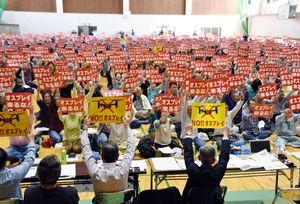 オスプレイ配備計画反対のプラカードを掲げる参加者たち=佐賀市川副町のスポーツパーク川副体育センター
