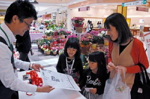 母の日に贈る誕生日の新聞を受け取る買い物客=佐賀市巨勢町のモラージュ佐賀