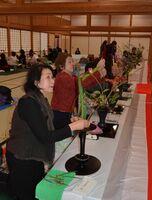 真剣な表情で花を生けていく会員ら=佐賀市の佐賀城本丸歴史館外御書院