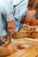 竹とんぼの羽の形に竹を削る岩本重男さん=小城市芦刈町の匠美建築工房作業場