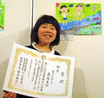 銀賞を受賞し、作品と記念撮影する開成小3年の森永美紀さん=佐賀市立図書館