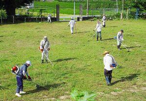 毎年、草むしりに取り組む地域住民たち=唐津市相知町の旧田頭小グラウンド(提供)