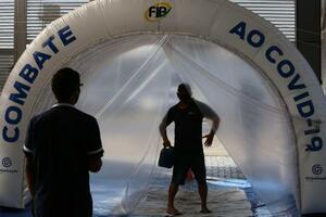 市場に入る前に消毒用のトンネルをくぐる人=3日、ブラジリア(AP=共同)