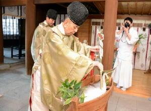 神社に奉納されたブリに御神矢で切り目を入れる「調理の儀」を行う草場昭司宮司=佐賀市の佐嘉神社