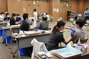 新型コロナウイルスワクチンの集団接種をする医師や看護師ら=佐賀市の県医療センター好生館