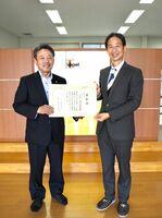 ヘルスケア産業づくり貢献大賞の特別賞の表彰状を受け取ったアイティーインペルの田中政史社長(左)=佐賀市の同社