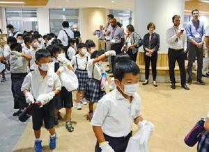 避難する児童の様子を視察する海外の専門家たち=東松浦郡玄海町の玄海みらい学園