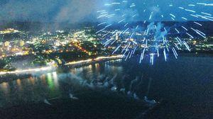 色鮮やかな打ち上げ花火の眼下には、唐津の夜景が広がる=唐津市西の浜(ドローンで空撮)