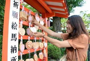 絵馬に恋愛成就の願いを込め、奉納するタイ人観光客の女性=鹿島市の祐徳稲荷神社