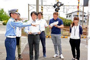 踏切や道路での注意点を指導する神埼署員(左)=神埼郡吉野ヶ里町吉田