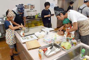 包丁などの調理器具を使って調理する参加者たち=佐賀市のアバンセ