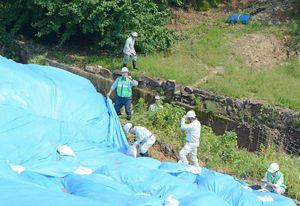 ブルーシートで覆われた被害箇所の状況を確認する九州農政局の担当者ら=三養基郡基山町の亀の甲ため池