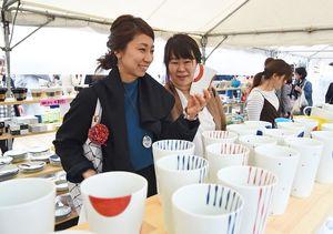 商品を手にし、相談しながら焼き物を選ぶ陶器市客=4月29日、有田町