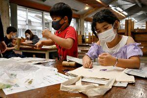 木づちで布に草花を染めながらエコバッグを作る参加者=佐賀市富士町の北山少年自然の家