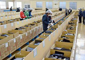 初入札の後、ノリの出来を確かめ合う漁業者=佐賀市の佐賀県有明海漁協