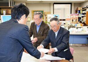 佐賀県危機管理防災課の担当者(左)に要請書を手渡す田口常幸共同代表=県庁