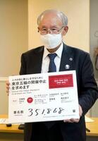 集まった署名の数を書いたボードを手にする宇都宮健児氏=14日午前、東京都庁