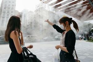 厳しい暑さの中、ミストの下で涼む人たち=7日午後、東京・銀座