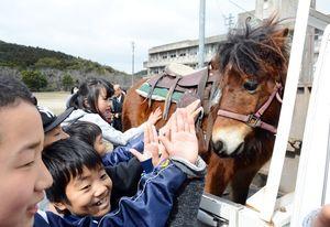 軽トラックに乗せられて行くチャロを見送る児童たち=唐津市の大良小