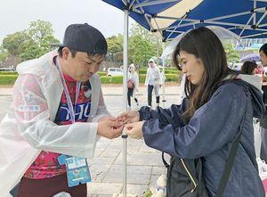 手作りミサンガを手渡す田上涼華さん(右)とサポーター=鳥栖市のベストアメニティスタジアム