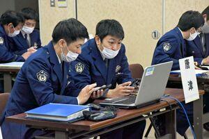 サイバー犯罪捜査に関する問題に2人一組で臨む警察官=佐賀市の県警本部