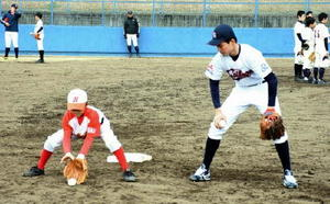 西部ガスの選手(右)から捕球時の姿勢のアドバイスを受ける中学生=伊万里市の国見台野球場