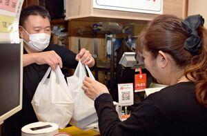 出来上がった弁当を手渡す井手潔店長(左)。新たに「持ち帰りメニュー」を設けた=武雄市の居食亭「豊」