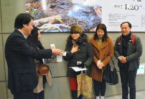 来場2万人目を記念して、サガテレビの大森伸昭取締役(左)から池田学さんのサイン入り図録をプレゼントされる康南姫さん(右から3人目)=佐賀市の県立美術館