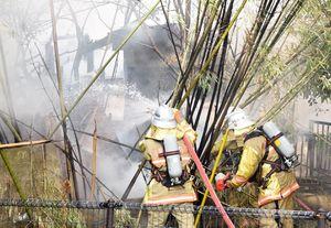 火の手が上がった民家へ放水する隊員ら=1日午前9時50分、佐賀市多布施1丁目
