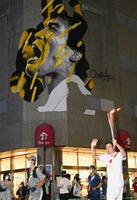 古賀稔彦さんの巨大壁画を掲げる百貨店前を走る聖火ランナー=10日夜、佐賀市