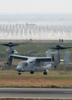 佐賀空港の滑走路上空で試験飛行をする在沖縄米軍のオスプレイ。奥はノリ養殖の網を張った支柱が林立している有明海=2016年11月8日、佐賀市川副町