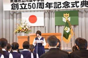 川登中創立50周年記念式典で生徒を代表して誓いの言葉を述べる秀野ひかりさん(中央)=川登中学校体育館